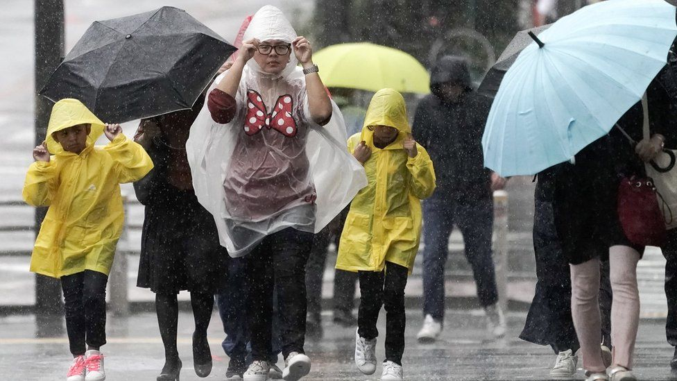 Pedestrians struggle against rain and wind in Tokyo, Japan, 12 October 2019