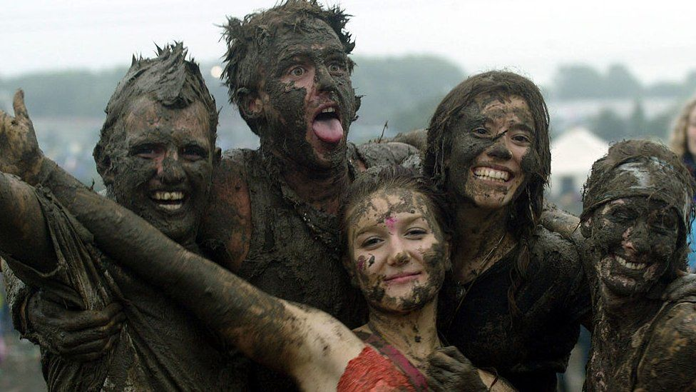 Festival go-ers covered in mud