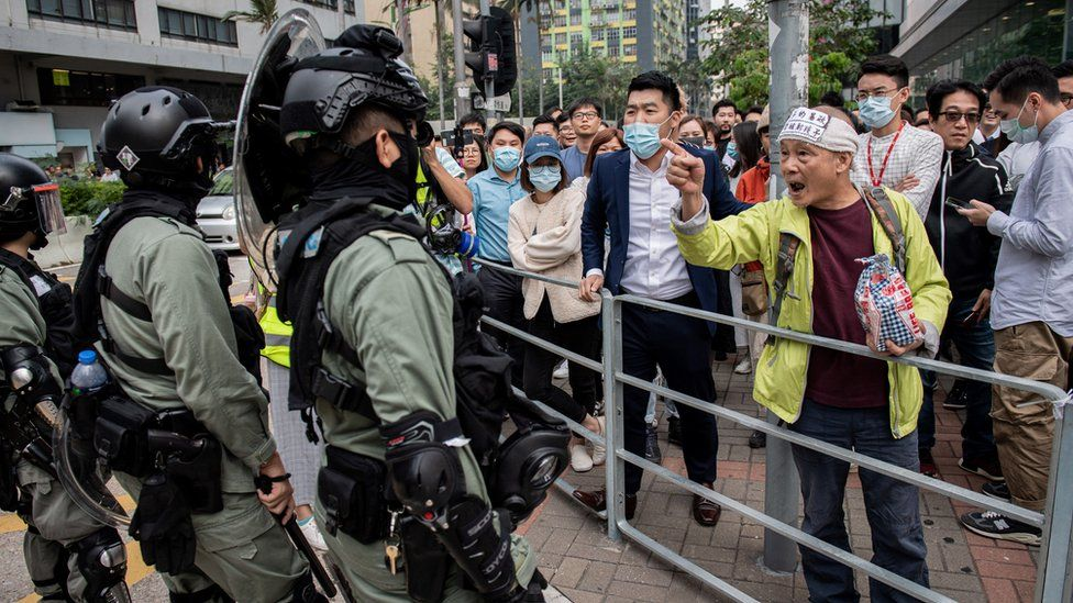 Riot police (L) arrive to disperse people gathering in support of pro-democracy protesters during a lunch break rally in the Kowloon Bay area in Hong Kong on November 26, 2019