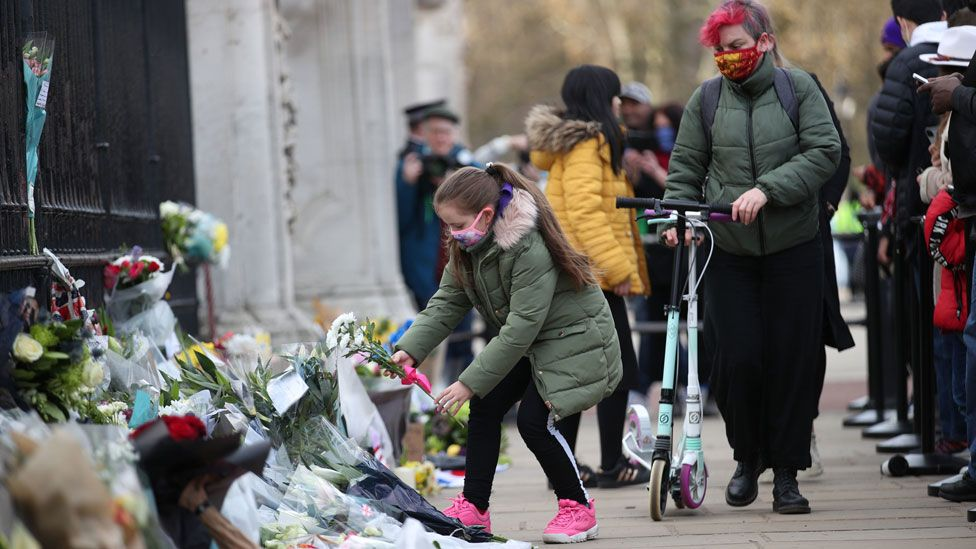Child places flowers outside Buckingham Palace