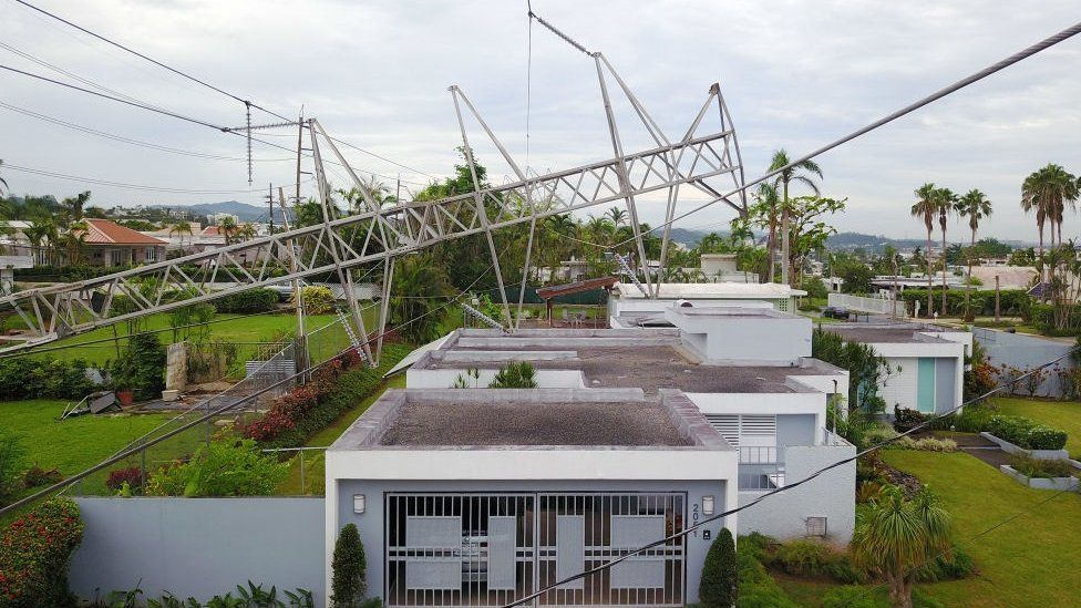 A power line tower downed by the passing of Hurricane Maria lies on top of a house in San Juan, Puerto Rico on November 7, 2017