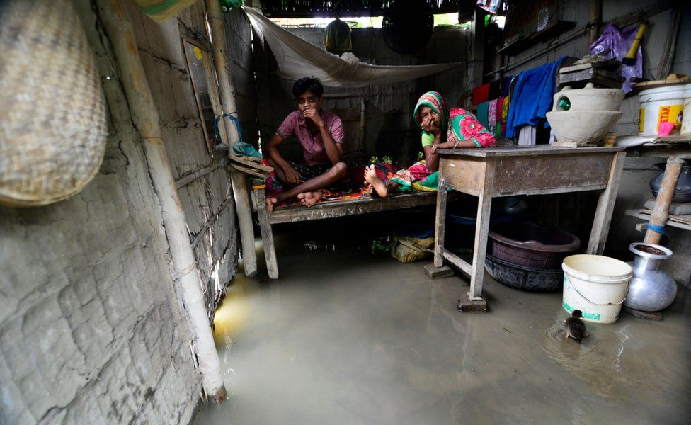 A couple sits on a bed as their home is inundated by flood waters in the flood affected Morigaon district of Assam, India, 12 July 2019