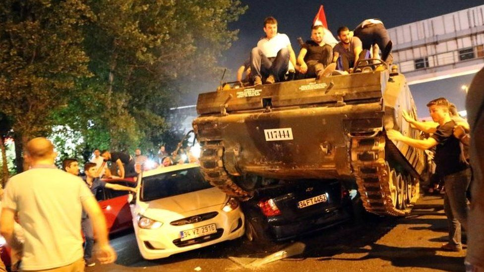 People on a tank run over cars on a road in Istanbul, Turkey, 16 July 2016