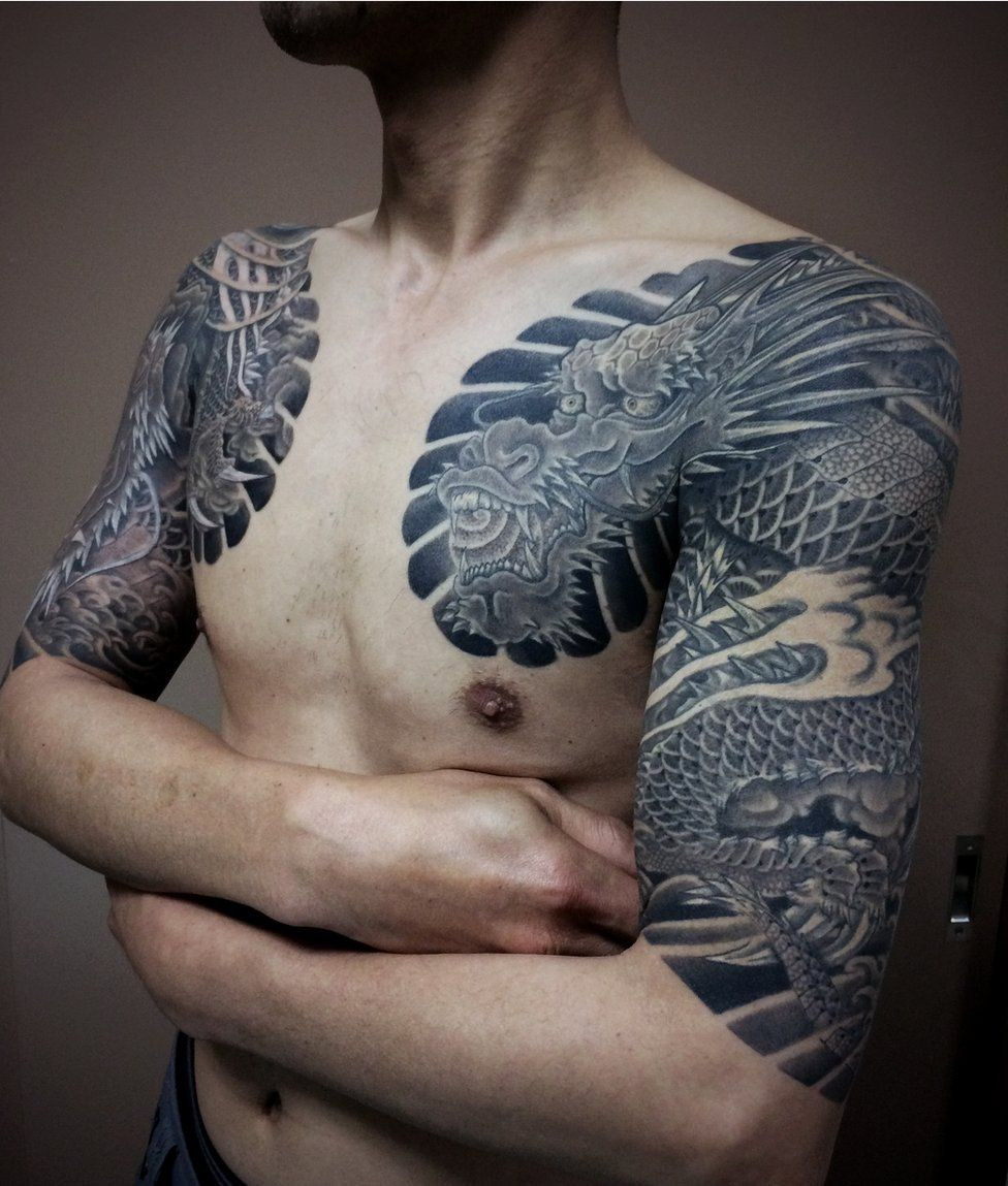 A man displays dragon tattoos on his upper arms and chest