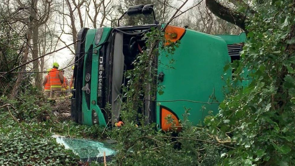 Bin lorry on its side with emergency services personnel on the scene