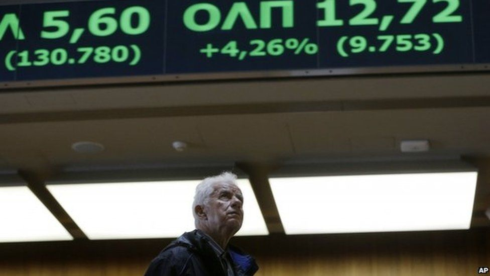 An elderly man looks at rising stocks in green at the Stock Exchange in Athens on Monday, June 22, 2015