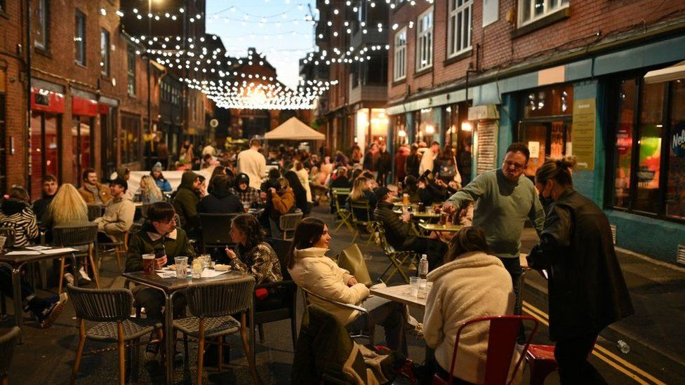 Customers enjoy drinks outside the bars in the Northern Quarter of central Manchester