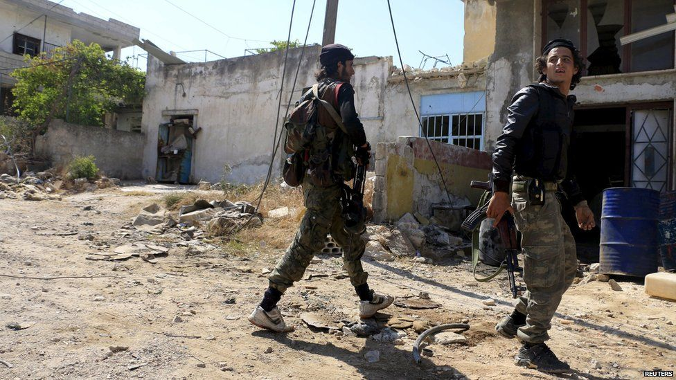 Rebel fighters walk through the town of Psoncol in Idlib province, Syria (6 June 2015)
