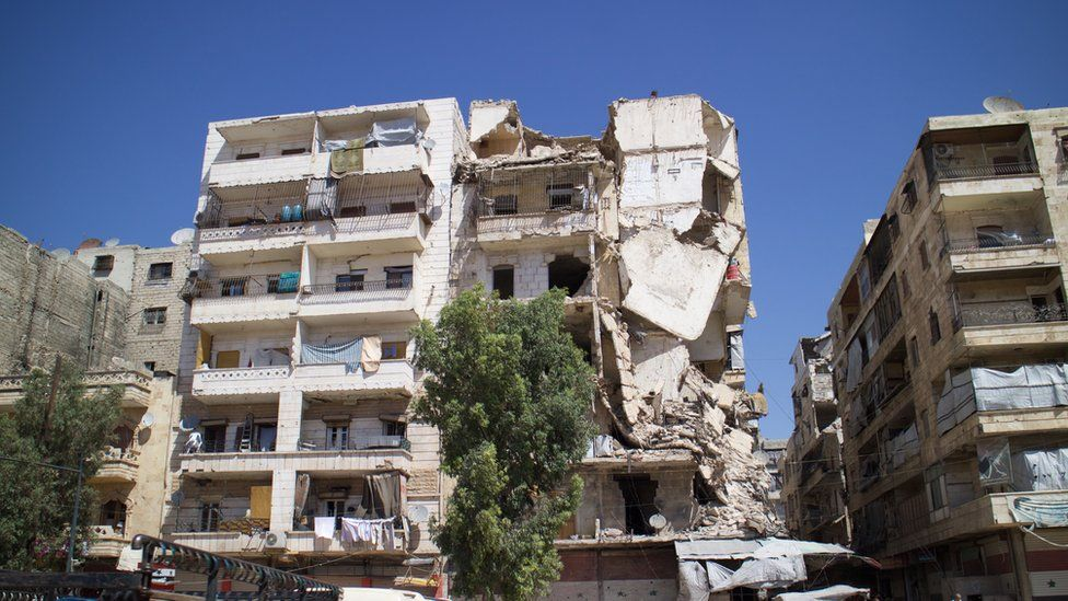 Damage from a few years ago in west Aleppo. Area is now considered a little safer. Families have moved into flats in badly damaged, unsafe buildings. Serious housing crisis. Winters here are cold.