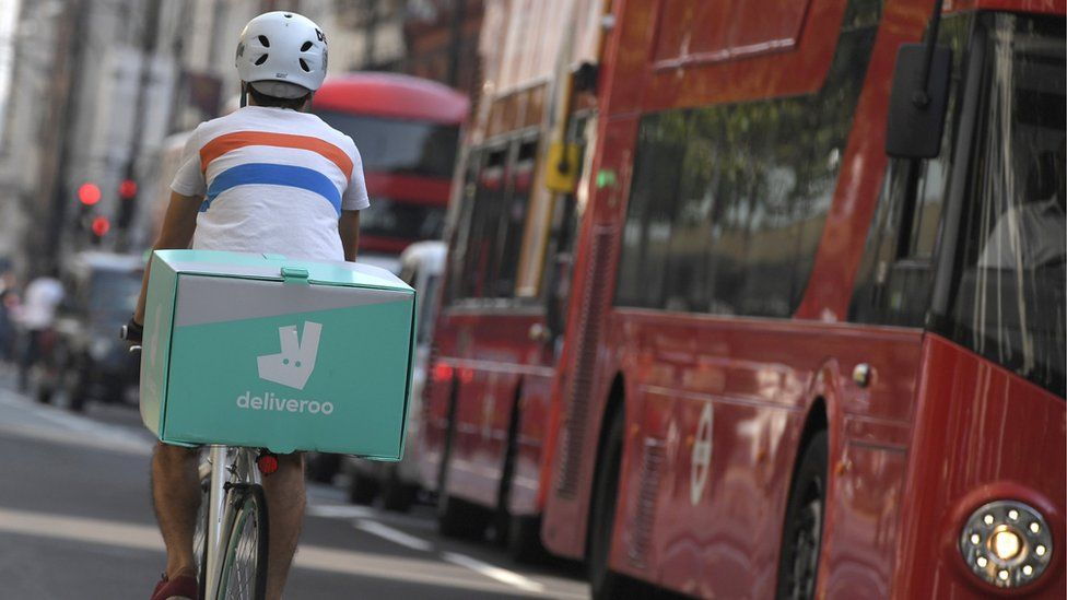 A bicycle courier with a box bearing the logo of Deliveroo rides through the streets of London with the city's iconic red buses visible nearby