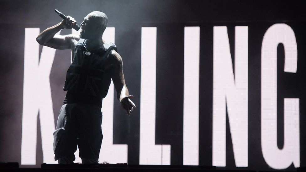 """Stormzy in front of a screen that reads """"Killing"""""""