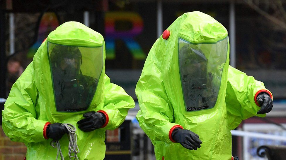 Two people wearing green protective suits involved in the investigation in Salisbury.