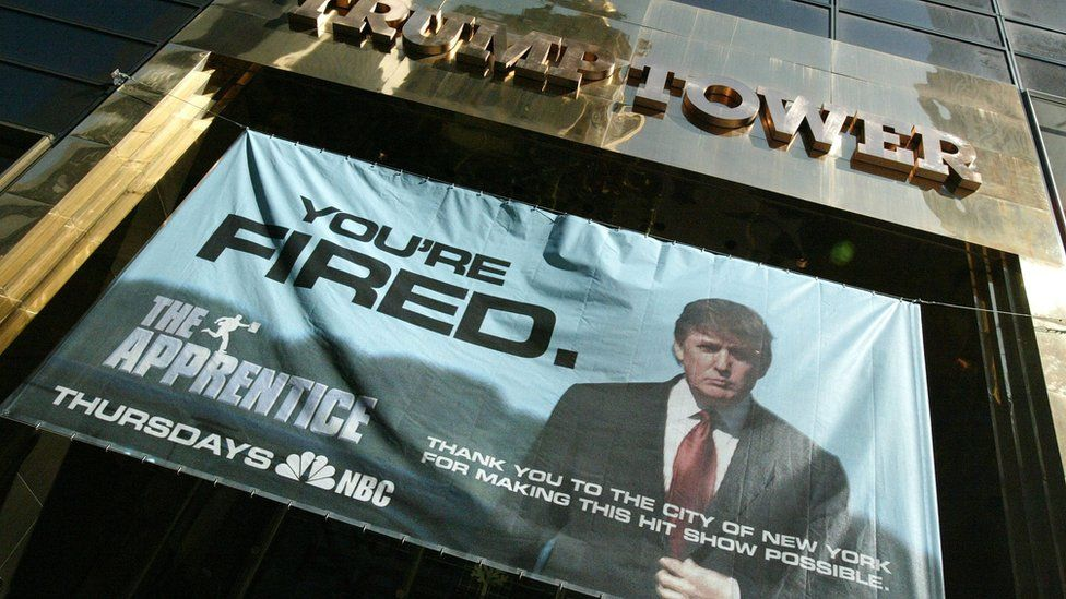 "A sign with the slogan YOU'RE FIRED advertising the American television show ""The Apprentice"" starring Donald Trump hangs at Trump Towers April 15, 2004 in New York City"