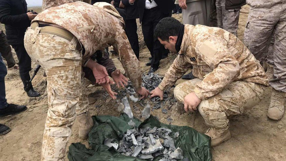 Security forces retrieve debris from a crater reportedly caused by an Iranian missile in Bardah Rashsh, in Iraq's Kurdistan Region