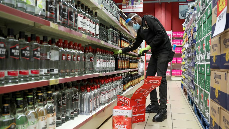A worker restocking alcohol shelves in June in South Africa