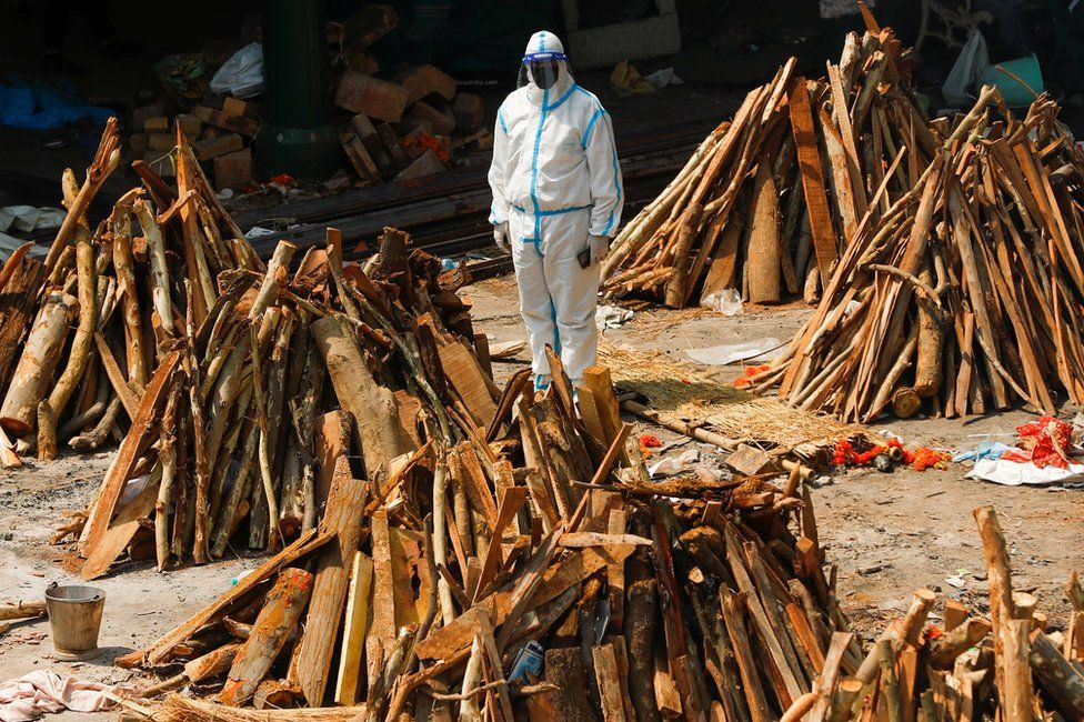 A man wearing personal protective equipment (PPE) stands next to funeral pyres in New Delhi, India
