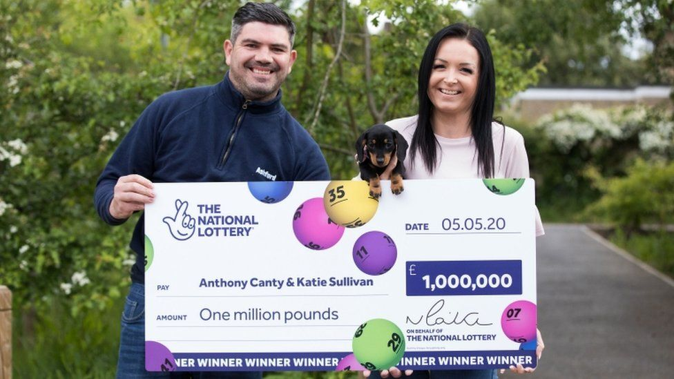 Anthony Canty, Katie Sullivan and Lucky Lola the dachshund with a giant cheque