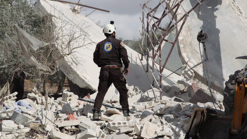 A Syrian first responder from the White Helmets group stands at the scene of a reported air strike in Jaballa (2 November 2019)