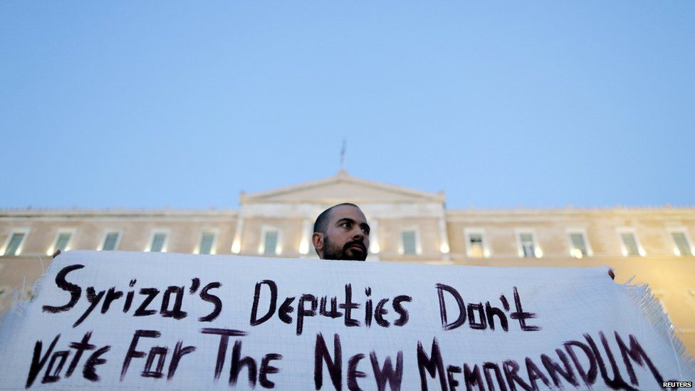An anti-EU protester holds a banner in front of the parliament building in Athens