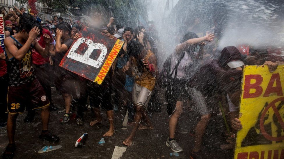 Philippine protesters are soaked by riot police while marching against Donald Trump's visit