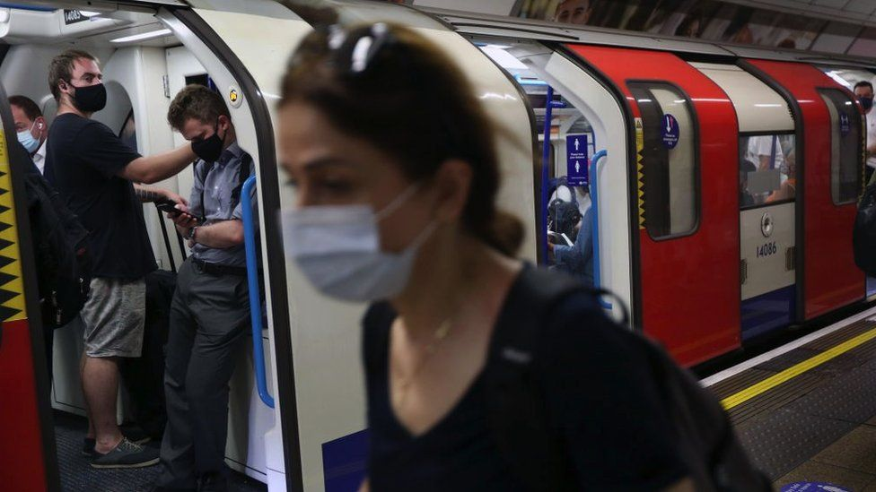 A person wearing a face mask by a Tube train