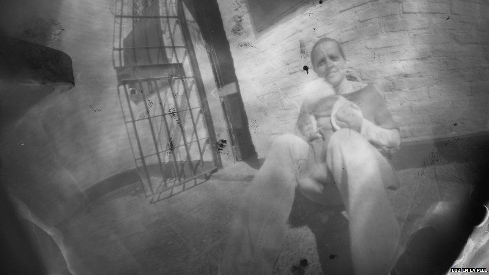 A pinhole photograph of a woman holding a baby