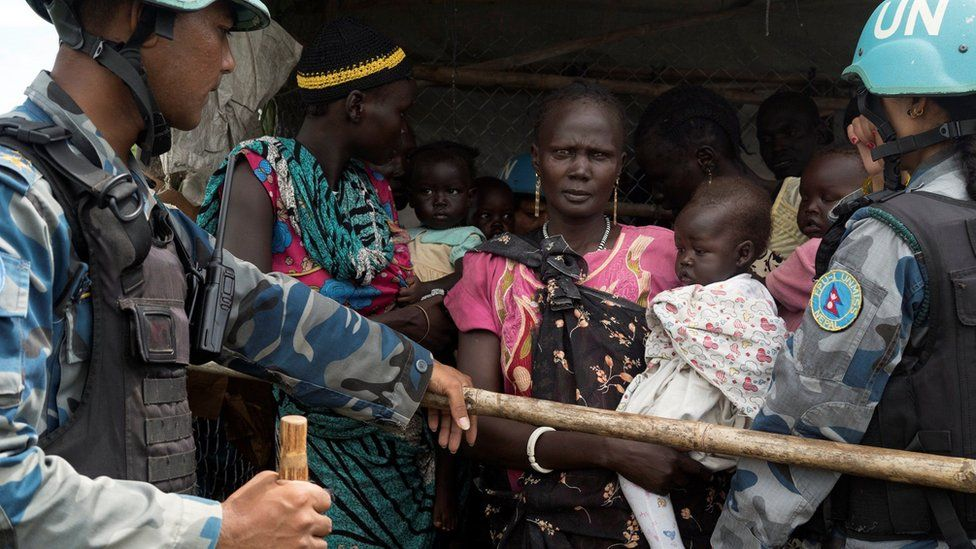United Nations peacekeepers control South Sudanese women and children before the distribution of emergency food supplies at the United Nations protection of civilians (POC) site - July 2016