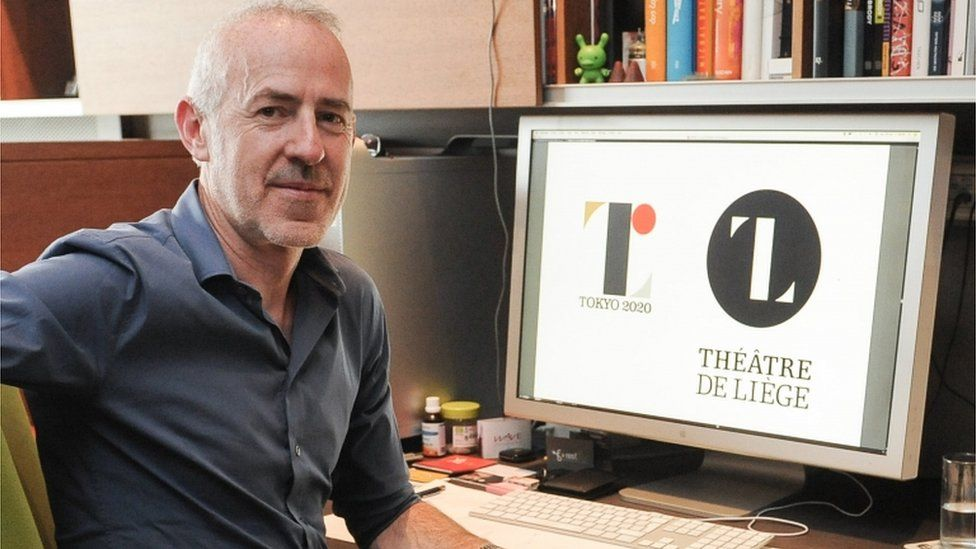 """Belgian Designer Olivier Debie poses for a photographer in his office in Liege on July 30, 2015 as his computer display shows Tokyo""""s 2020 Olympic emblem (L) and the logo of the Theatre de Liege."""
