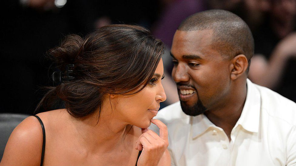 Kim Kardashian and rapper Kanye West talk from courtside seats in 2012