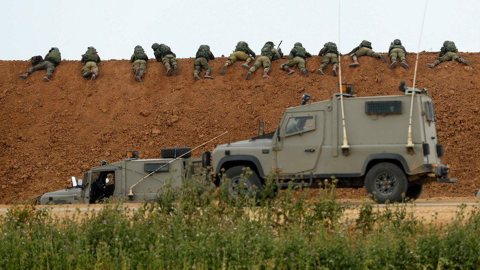 Israeli soldiers lie along an earth barrier along the border with the Gaza strip in the southern Israeli kibbutz of Nahal Oz on March 30, 2018