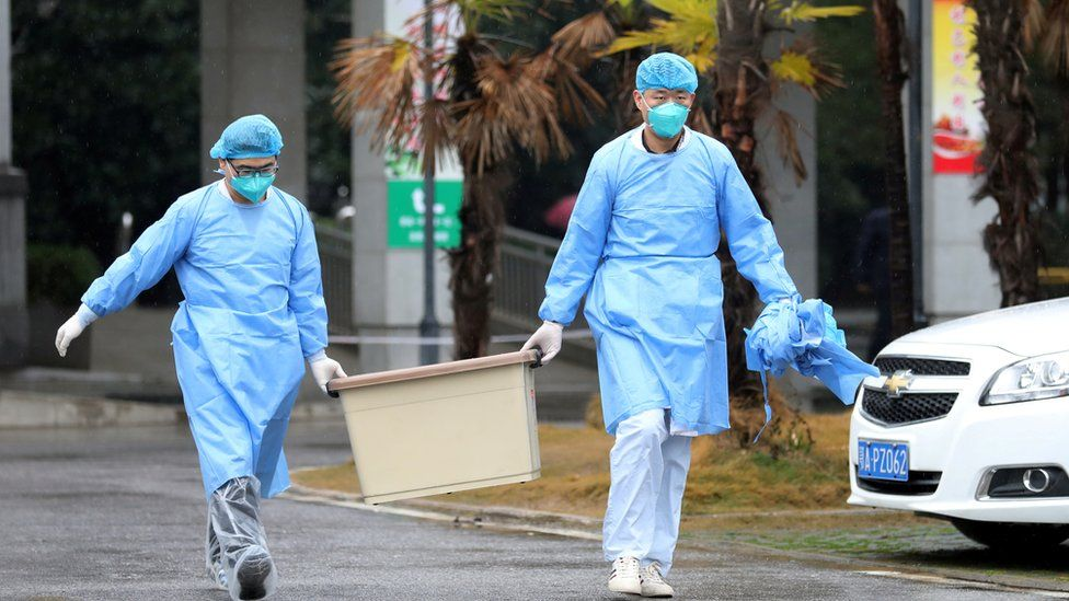 Medical staff carry a box as they walk at the Jinyintan hospital, where the patients with pneumonia caused by the new strain of coronavirus are being treated, in Wuhan, Hubei province