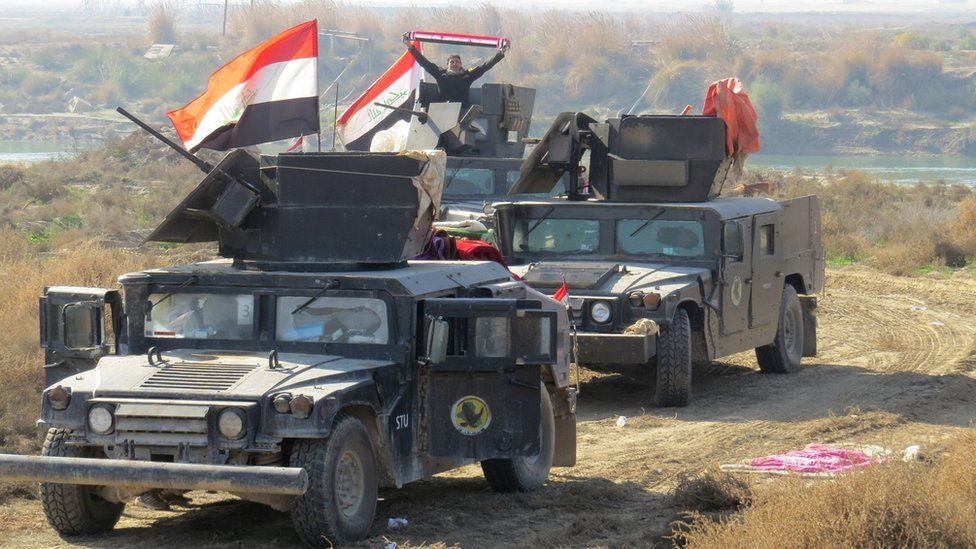 Iraqi pro-government forces display national flags in the al-Aramil area, south of Ramadi (22 December 2015)