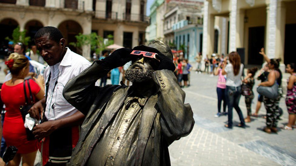 A street performer looks towards the sky as enthusiasts gather in Old Havana for the partial solar eclipse in Cuba August 21, 2017.