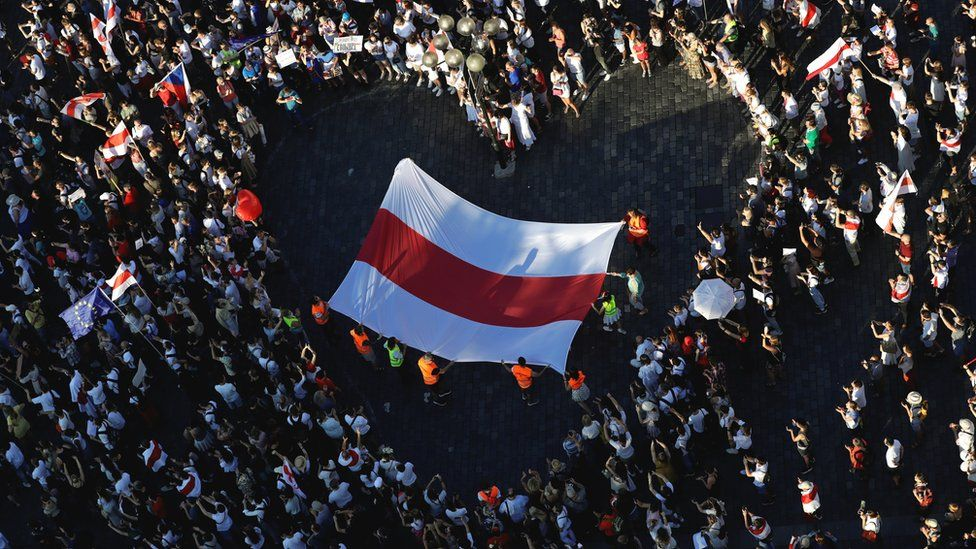 A large historical white-red-white flag of Belarus is pictured inside a heart formed by demonstrators