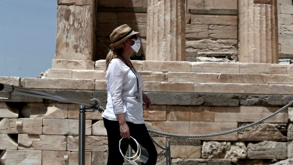 A woman wears a mask at the archaeological site of the Acropolis hill in Athens, 18 May 2020