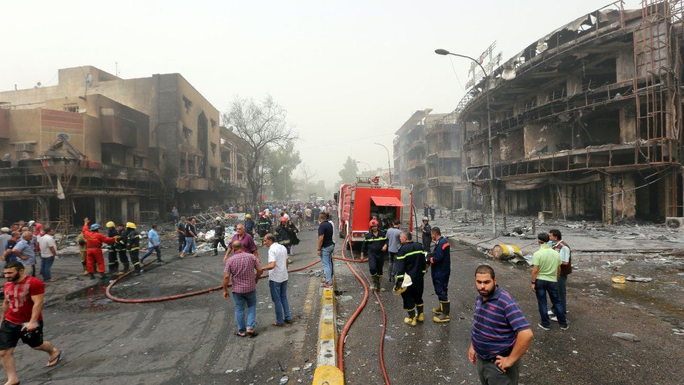 Iraqis, including firefighters, gather at the site of a suicide car bombing claimed by the Islamic State group on July 3, 2016 in Baghdad's central Karrada district