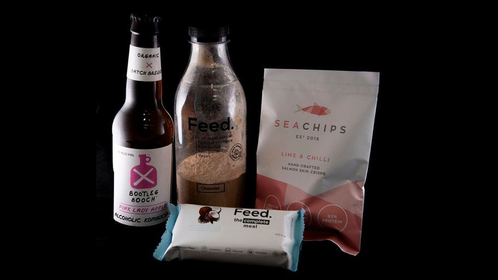 Alcoholic kombucha, a coconut and chocolate meal bar, salmon skin crisps and a powdered chocolate meal drink.