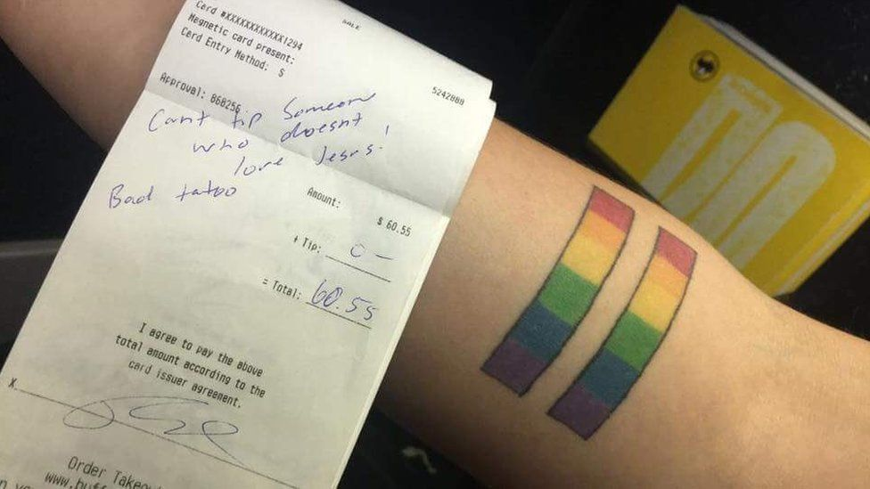 Receipt which says 'Can't tip someone who doesn't love Jesus! Bad tattoo,' placed next to a rainbow equal sign tattoo