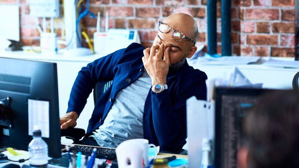 Man at desk looking stressed out