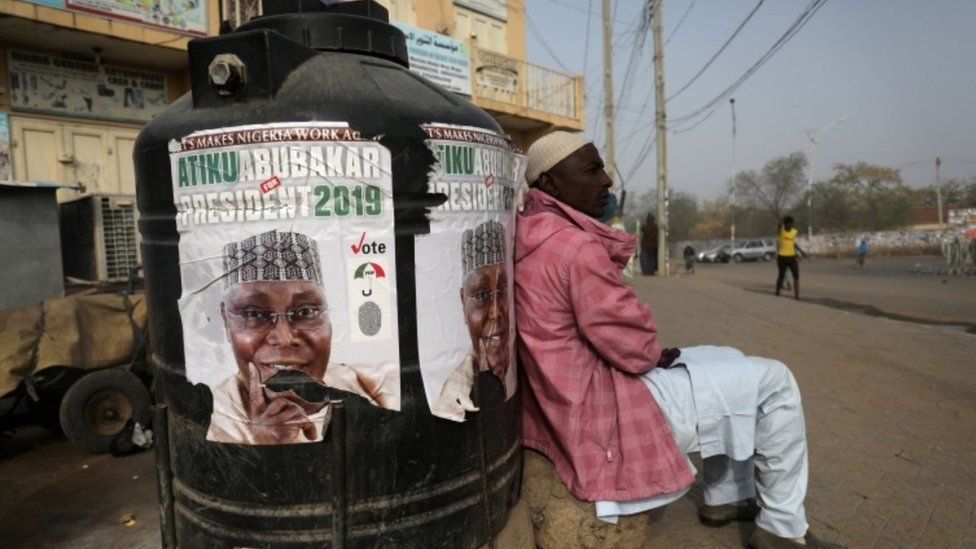 """A man sits next to a campaign poster of Atiku Abubakar, leader of the People""""s Democratic Party (PDP), after the postponement of the presidential election in Kano, Nigeria February 17, 2019. REUTERS/Luc Gnago"""