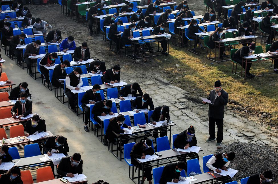 Students maintaining social distance and wearing protective face masks attend their grade 12 exams, in Kathmandu, Nepal