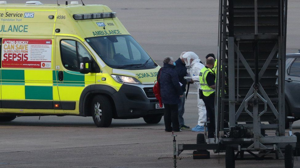 A member of the NHS West Midlands Ambulance Service, wearing protective clothing and a face mask, speaks to passengers (left) from the coronavirus-hit Grand Princess cruise ship after they arrived at Birmingham Airport following their repatriation to the UK from the US