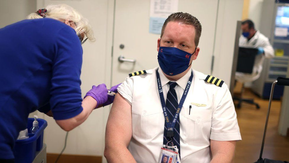 pilot wearing masked and being vaccinated