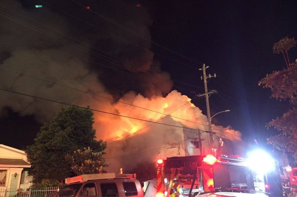 Flames rise from the top of a warehouse, which caught fire during a dance party in Oakland, California,U.S. December 3, 2016.