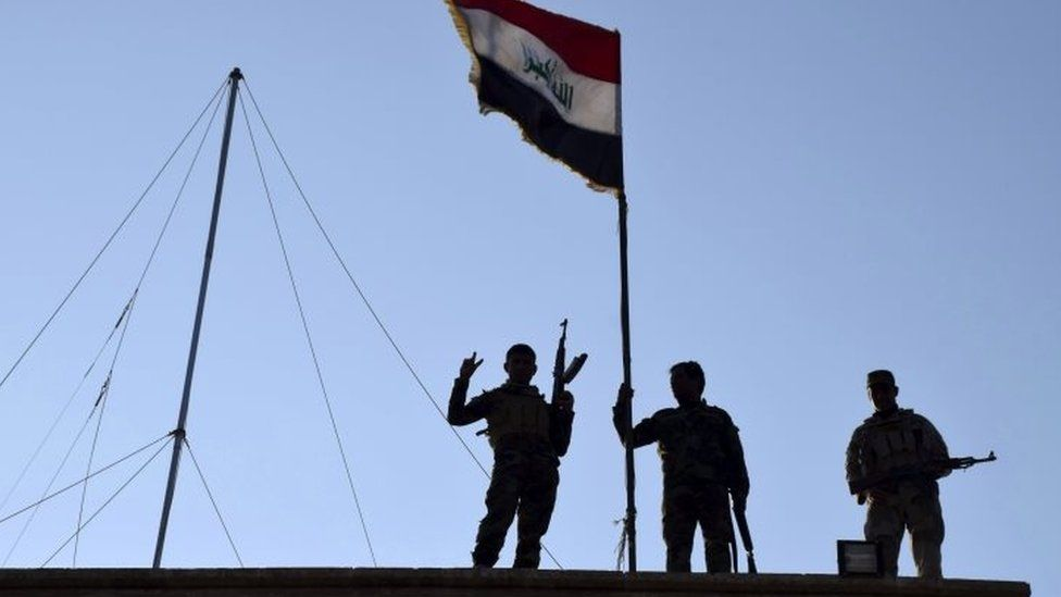 Iraqi soldiers raise the national flag over a government building in Ramadi. Photo: 21 December 2015