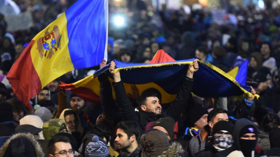 People wave flags during a protest in front of the government headquarters in Bucharest against controversial decrees to pardon corrupt politicians and decriminalize other offenses on February