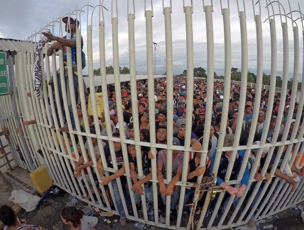[Imagem: _103940042_migrantsgate.jpg]