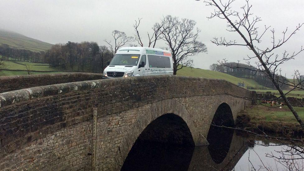 A Little White Bus service in north Yorkshire crosses a stone bridge