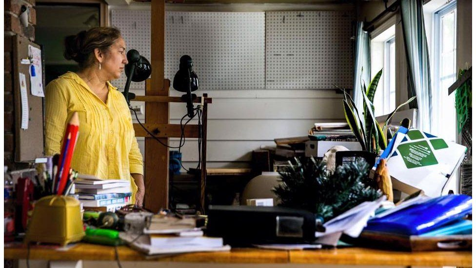 """Rosanna Sigue, 59, surveys what was once her personal painting studio after her recent retirement from decades of teaching. """"I've never felt such loss. Not even for all of the stuff, but losing my father's voice."""" Her father, who passed away, was recorded on a device that is now ruined by the flood water. Baton Rouge, La"""