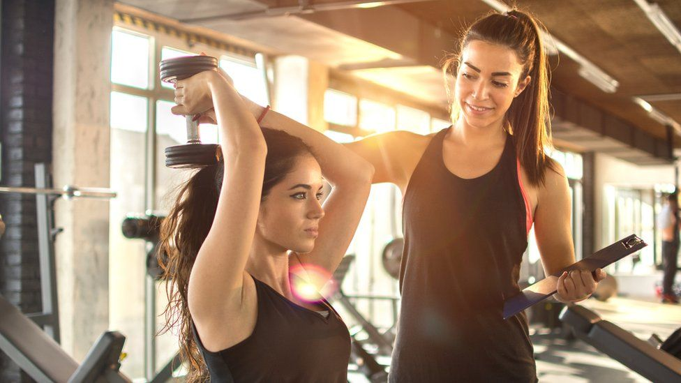 A personal trainer helps a woman lift a weight behind her head in the gym